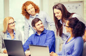Smiling team with laptop computers in office — Stock Photo