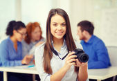Smiling female photographer with photocamera — Stock Photo