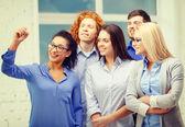 Smiling creative team writing on virtual screen — Stock Photo