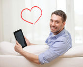 Smiling man working with tablet pc at home — Stockfoto