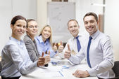Business team showing thumbs up in office — Foto Stock