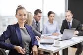Businesswoman with glasses with team on the back — Stock Photo