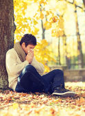 Ill man with paper tissue in autumn park — Stockfoto