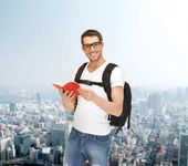 Travelling student with backpack and book — Stockfoto