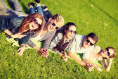 Group of students or teenagers lying in park — Stockfoto