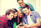 Students looking at smartphone at school — Stock Photo