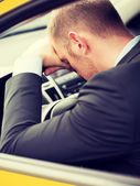 Tired businessman or taxi car driver — Stock Photo