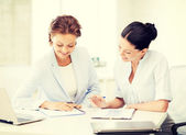 Two smiling businesswomen working in office — Stock Photo