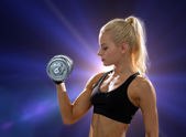 Young sporty woman with heavy steel dumbbell — Photo