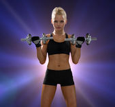 Sporty woman with heavy steel dumbbells — Stock Photo