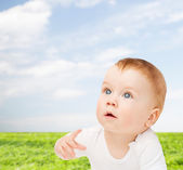Curious baby lying on floor and looking up — Stock Photo