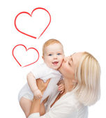 Happy mother kissing smiling baby — Stok fotoğraf