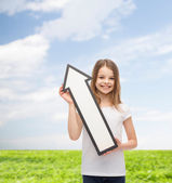 Smiling little girl with blank arrow pointing up — Stock Photo