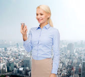Young smiling businesswoman with smartphone — Stok fotoğraf