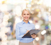 Smiling businesswoman with clipboard and pen — Stock Photo