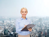 Smiling businesswoman with clipboard and pen — Photo