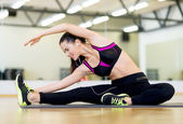 Stretching young woman with earphones in the gym — Stock Photo