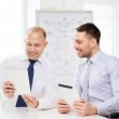 Two smiling businessmen with tablet pc in office — Stock Photo
