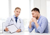 Doctor with clipboard and patient in hospital — Stockfoto