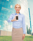 Smiling businesswoman with smartphone blank screen — 图库照片