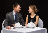 Smiling couple looking at each other at restaurant — Stock Photo
