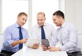 Three smiling businessmen with tablet pc in office — Stock Photo