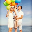 Happy family with colorful balloons at seaside — Stock Photo #48940113