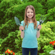 Smiling little girl with rake and scoop — Stock Photo #48946141