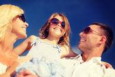 Happy family in sunglasses over blue sky — Stock Photo