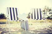 Two beach lounges with beach bag and white hat — Stock Photo
