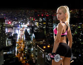 Sporty woman with heavy steel dumbbells — Stockfoto