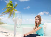 Smiling little girl with big fan at home — Stock Photo