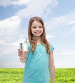 Smiling little girl giving glass of water — Stock Photo
