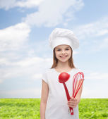 Smiling girl in cook hat with ladle and whisk — Stockfoto