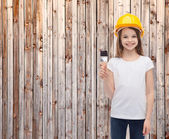Smiling little girl in helmet with paint roller — Foto Stock
