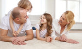 Parents and two girls lying on floor at home — Stockfoto