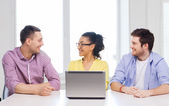 Three smiling colleagues with laptop in office — Stock Photo