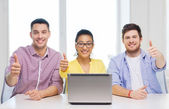 Three smiling colleagues with laptop in office — Foto Stock