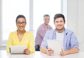 Smiling team with tablet pc computers at office — Stock Photo