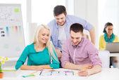 Diseñadores de interiores sonrientes trabajando en oficina — Foto de Stock