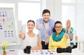 Smiling team with photocamera in office — Stock Photo