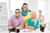 Smiling team with printed photos working in office — Foto Stock