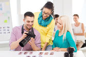 Smiling team with photocamera working in office — Foto Stock