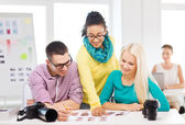 Smiling team with printed photos working in office — Stock Photo