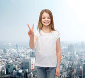 Little girl in white t-shirt showing peace gesture — Stock Photo