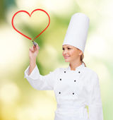 Smiling female chef writing something on air — Stock Photo