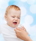 Crying baby with dummy — Stock Photo