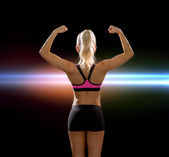 Sporty woman from the back flexing her biceps — Stok fotoğraf