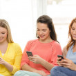 Smiling teenage girls with smartphones at home — Stock Photo #49091395