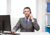 Helpline operator with headphones and computer — Stock Photo